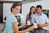 Smiling waitress giving coffee to a couple at coffee shop