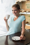 Smiling woman drinking coffee at counter in coffee shop