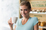 Smiling woman drinking coffee in the coffee shop