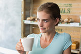 Thoughtful woman drinking coffee in coffee shop