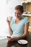 Woman drinking coffee while using mobile phone at counter in coffee shop