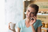 Woman drinking coffee while using mobile phone in coffee shop