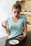 Shocked woman with coffee cup reading text message in coffee shop