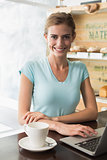 Smiling woman with coffee cup using laptop in coffee shop
