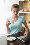 Woman with coffee cup using laptop in coffee shop