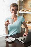 Smiling woman with coffee cup using laptop at coffee shop