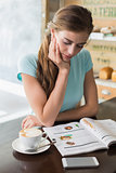 Concentrated woman with coffee cup reading magazine in coffee shop