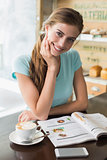 Smiling woman with coffee cup reading magazine in coffee shop