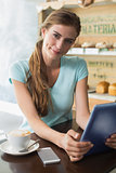 Woman with coffee cup using digital tablet in coffee shop
