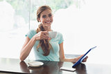 Smiling woman with coffee cup using digital tablet in coffee shop