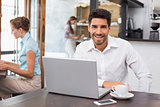 Smiling man using laptop in the coffee shop
