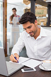 Man writing notes with laptop in coffee shop