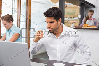 Man drinking coffee while using laptop in coffee shop