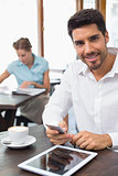 Smiling man text messaging in coffee shop