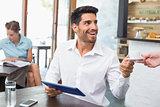 Man receiving coffee while using digital tablet in coffee shop