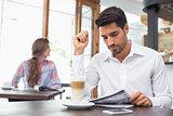 Man reading newspaper in coffee shop