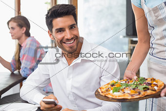 Waitress giving pizza to a smiling man at coffee shop