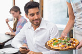 Waitress giving pizza to man at coffee shop