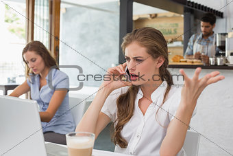 Annoyed woman using mobile phone in coffee shop