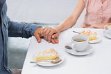 Mid section of couple holding hands at coffee shop