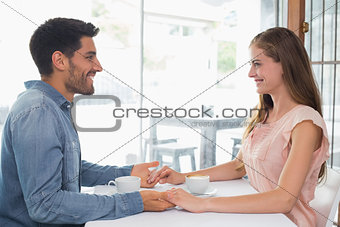 Romantic couple holding hands at coffee shop