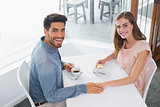 Romantic young couple holding hands at coffee shop