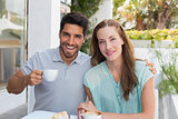 Smiling young couple with coffee cup at café
