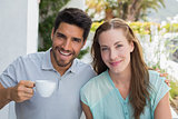 Smiling couple with coffee cup at café