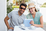 Smiling couple using digital tablet at café