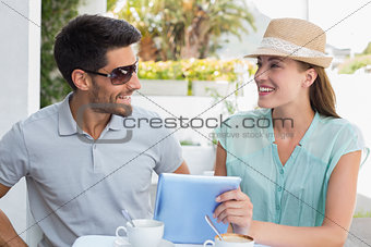 Smiling young couple using digital tablet at café