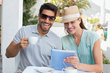 Smiling couple with coffee cup using digital tablet at café