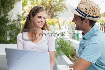 Smiling young couple using laptop at café