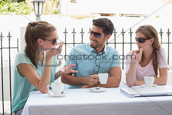 Three happy friends having coffee in café