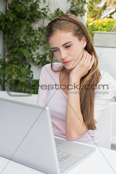 Beautiful woman using laptop at café