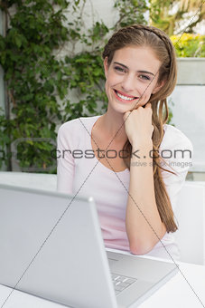 Beautiful young woman using laptop at café