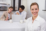 Businesswoman with colleagues in meeting at office desk