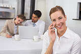 Businesswoman using mobile phone with colleagues at office desk