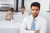 Confident businessman with colleagues at office desk