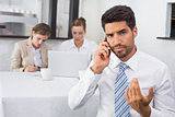 Businessman using mobile phone with colleagues at office desk