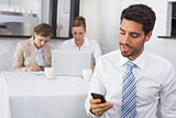 Businessman text messaging with colleagues at office desk