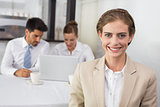 Smiling businesswoman with colleagues at office desk