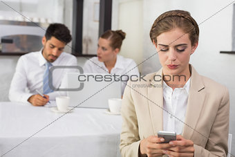 Businesswoman text messaging with colleagues at office desk