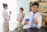 Businessman with coffee sipper gesturing thumbs up in office cafeteria