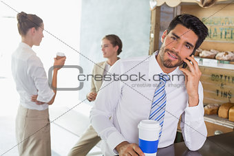 Businessman using mobile phone in office cafeteria