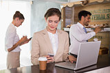 Businesswoman using mobile phone and laptop in office cafeteria