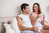 Relaxed couple having coffee in bed