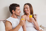 Happy relaxed couple with orange juices in bed