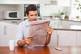 Concentrated man reading newspaper in kitchen
