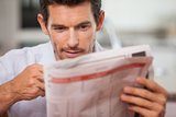 Concentrated young man reading newspaper
