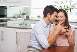 Couple with wine glasses sitting in kitchen